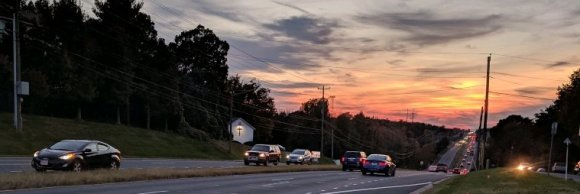 Image showing two lane road, with sunset, sky is orange, almost dark, with streetlight on.